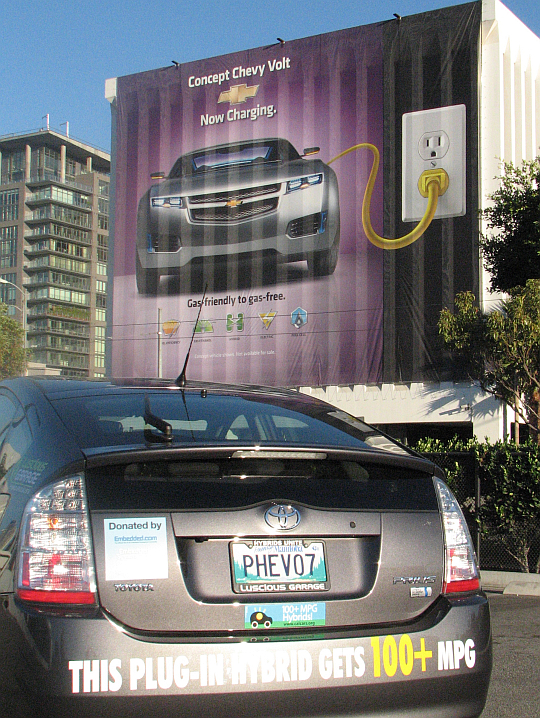 CalCars' Prius converted at LA Auto Show November 2007 in front of an ad for GM's Chevy Volt PHEV.